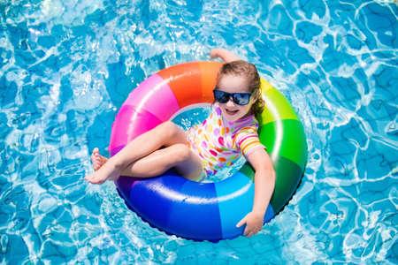 Glückliches kleines Mädchen mit bunten aufblasbaren Ring im Freibad an heißen Sommertagen zu spielen. Kinder schwimmen lernen. Kinder Sonnenschutz Hautausschlag Wache tragen in tropischen Resort entspannen Standard-Bild - 60370318