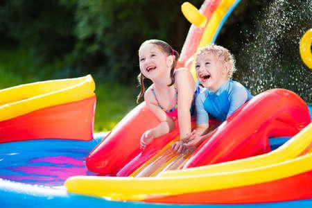 Bambini che giocano nella piscina gonfiabile per bambini. I bambini nuotano e sguazzano nel colorato centro giochi del giardino. Il ragazzo e la ragazza felici che giocano con l'acqua gioca il giorno di estate caldo. Famiglia divertendosi all'aperto nel cortile.