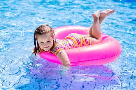 petite fille maillot de bain: Bonne petite fille jouant avec anneau gonflable coloré dans la piscine extérieure sur chaude journée d'été. Les enfants apprennent à nager. Enfants portant protection solaire éruption garde de détente dans la station tropicale