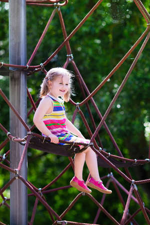 Active little child playing on climbing net and jumping on trampoline at school yard playground. Kids play and climb outdoors on sunny summer day. Cute girl on nest swing at preschool sport center. Stock Photo