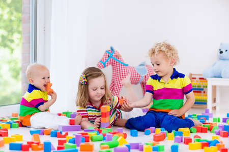 Happy preschool age children play with colorful plastic toy blocks. Creative kindergarten kids build a block tower. Educational toys for toddler or baby. Siblings having fun playing together. Stock Photo