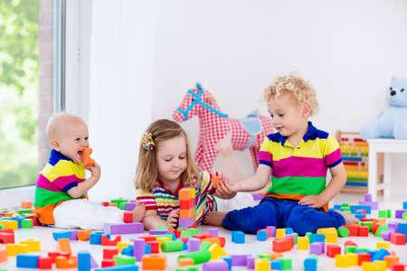 Heureux les enfants d'âge préscolaire jouent avec des blocs de jouets colorés en plastique. Creative maternelle les enfants construisent une tour de bloc. Jouets éducatifs pour enfant en bas âge ou un bébé. Les frères et s?urs ayant du plaisir à jouer ensemble. Banque d'images - 60416440