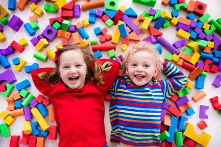 Glückliche Kinder im Vorschulalter spielen mit bunten Kunststoff-Spielzeug-Blöcke. Kreative Kindergartenkinder bauen einen Block Turm. Lernspielzeug für Kleinkind oder Baby. Draufsicht von oben.