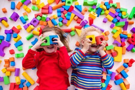Glückliche Kinder im Vorschulalter spielen mit bunten Kunststoff-Spielzeug-Blöcke. Kreative Kindergartenkinder bauen einen Block Turm. Lernspielzeug für Kleinkind oder Baby. Draufsicht von oben. Standard-Bild