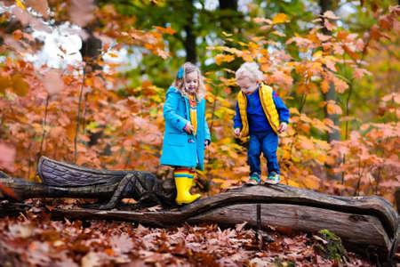 Gelukkige kinderen die in mooie herfst park op koude zonnige dag vallen. Kids in warme jassen spelen met gouden bladeren. Stockfoto