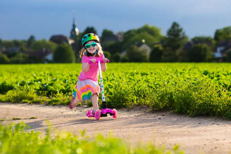 preschooler: Little child learning to ride a scooter in a city park on sunny summer day. Cute preschooler girl in safety helmet riding a roller. Kids play outdoors. Active leisure and outdoor sport for children.