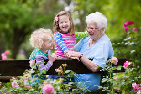 Happy senior lady playing with little boy and girl in blooming rose garden. Grandmother with grand children sitting on a bench in summer park with beautiful flowers. Kids gardening with grandparent. Stock Photo