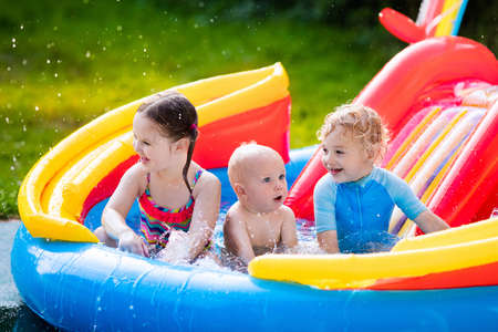 Children playing in inflatable baby pool. Kids swim and splash in colorful garden play center. Happy boy, girl and baby with water toys on hot summer day. Family having fun outdoors in the backyard.