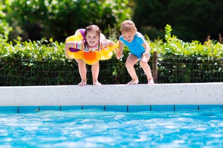 Bonne petite fille et garçon tenant la main de sauter dans la piscine extérieure dans un complexe tropical pendant les vacances d'été en famille. Les enfants apprennent à nager. Plaisirs de l'eau pour les enfants. Banque d'images