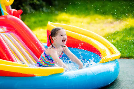hot day: Children playing in inflatable baby pool. Kids swim and splash in colorful garden play center. Happy little girl playing with water toys on hot summer day. Family having fun outdoors in the backyard.