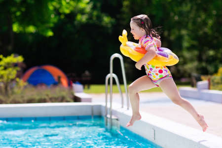 Happy little girl with inflatable toy ring jumping into outdoor swimming pool in a tropical resort during family summer vacation. Kids learning to swim. Water fun for children. Stock Photo