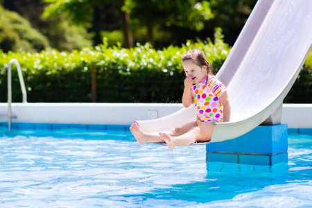 slide: Happy laughing little girl playing on water slide in outdoor swimming pool on hot summer day. Kids learn to swim. Child wearing sun protection rash guard sliding on aqua playground in tropical resort Stock Photo
