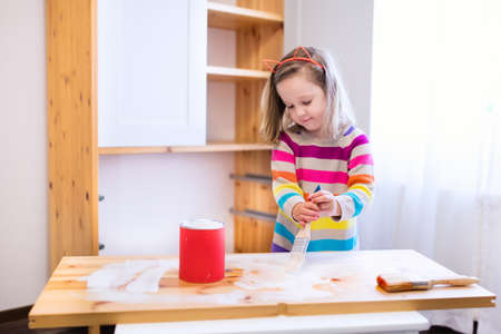 girl home: Happy preschool age girl holding a brush painting a wooden bedroom closet with white color paint. Child learning furniture renovation and restoration. Do it yourself project with kids at home. Stock Photo