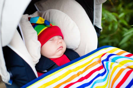 Cute little baby in funny colorful hat sleeping in infant car seat on a walk in a park Stock Photo