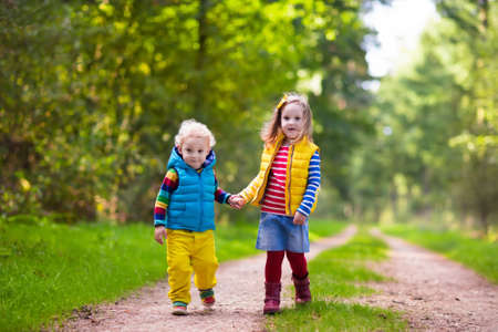 fashion boy: Kids playing in autumn park. Children play outdoors on a sunny fall day. Boy and girl running together hand in hand in a forest. Toddler and preschooler pick colorful oak leaf. Family fun outdoor