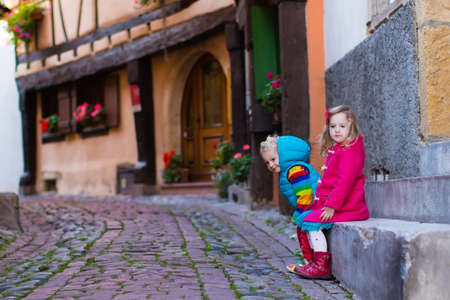winter fashion: Cute little girl and boy walking down a street in historical medieval city center on cold autumn day. Children during fall vacation in Eguisheim, Alsace, France. Travelling and tourism with kids. Stock Photo