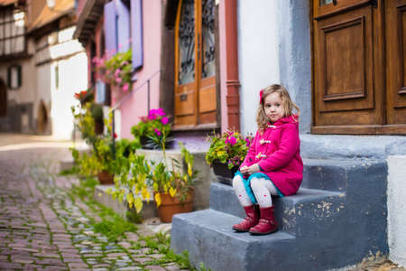 niñas pequeñas: Niña linda en capa rosada caminando por una calle en la histórica ciudad medieval en frío día de otoño. Niño durante las vacaciones de otoño en Eguisheim, Alsacia, Francia. Los viajes y el turismo con los niños.