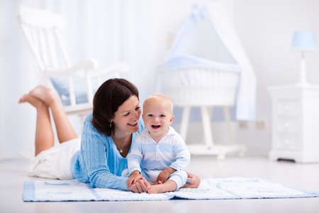 Happy young mother and adorable baby boy playing on a blue floor mat in a white sunny nursery with rocking chair and bassinet. Bedroom interior with infant crib. Mom and child on playmat at kids bed. Reklamní fotografie