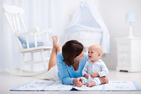 Happy young mother and adorable baby boy playing on a blue floor mat in a white sunny nursery with rocking chair and bassinet. Bedroom interior with infant crib. Mom and child on playmat at kids bed. Stock Photo