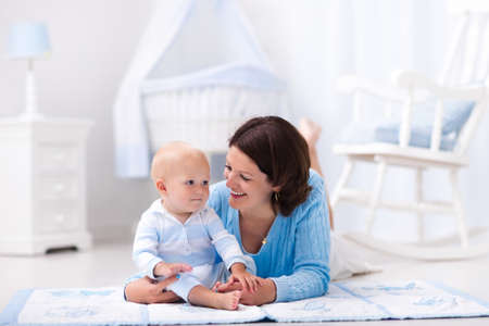 floor mat: Happy young mother and adorable baby boy playing on a blue floor mat in a white sunny nursery with rocking chair and bassinet. Bedroom interior with infant crib. Mom and child on playmat at kids bed. Stock Photo