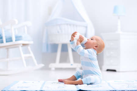 Adorable baby boy playing on a blue floor mat and drinking milk from a bottle in a white sunny nursery with rocking chair and bassinet. Bedroom interior with infant crib. Formula drink for infant. Stock Photo