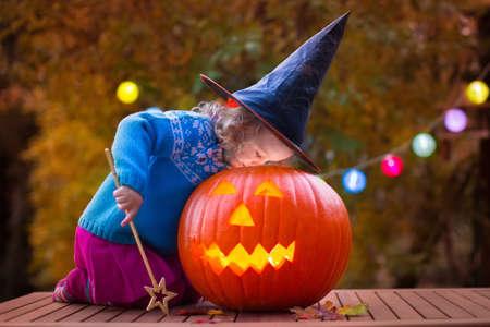 fruit orange: Niña y niño talla de calabaza en Halloween. Vestida niños truco o trato. Trick or treat Kids. Niño en el traje de juego bruja en el Parque de otoño. Niño del niño con jack-o-lantern. Foto de archivo