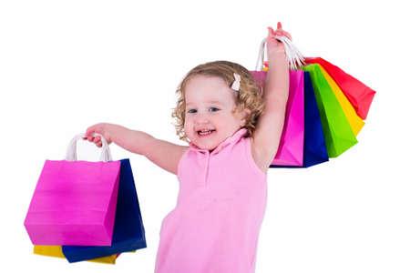 カラフルなショッピング バッグを保持しているピンクのドレスの少女。子供服を買ってお店で。店での販売。購入の子どもたち。