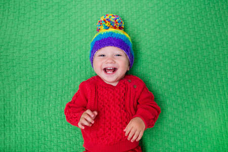 fleece: Cute baby in warm wool knitted hat on a red blanket. Autumn and winter clothing for young kids. Colorful knitwear for children. Adorable little boy ready for a walk on a cold fall day. Stock Photo