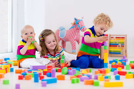 Happy preschool age children play with colorful plastic toy blocks. Creative kindergarten kids build a block tower. Educational toys for toddler or baby. Siblings having fun playing together. Stockfoto