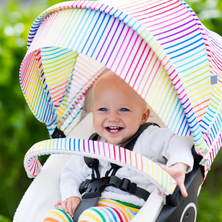 Baby boy in white sweater sitting in white stroller on a walk in a park. Child in colorful rainbow buggy. Little kid in a pushchair. Traveling with young kids. Transportation for family with infant. Reklamní fotografie - 61143417