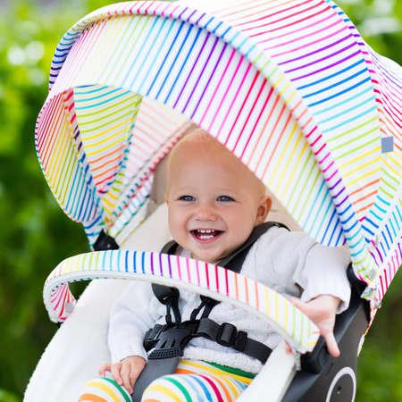 Baby jongen in de witte trui in witte wandelwagen op een wandeling in een park. Kind in kleurrijke regenboog buggy. Klein kind in een kinderwagen. Reist u met jonge kinderen. Vervoer voor gezin met kleine kinderen.