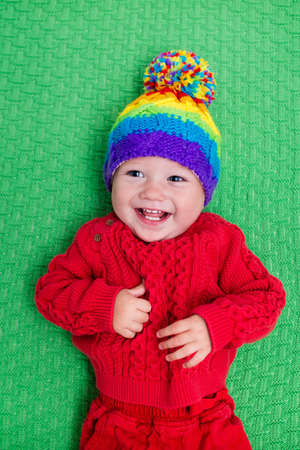 children clothing: Cute baby in warm wool knitted hat on a red blanket. Autumn and winter clothing for young kids. Colorful knitwear for children. Adorable little boy ready for a walk on a cold fall day. Stock Photo