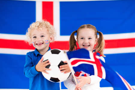 Children cheering and supporting Icelandic national football team. Kids fans and supporters of Iceland during soccer championship.