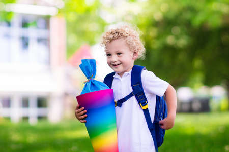 cone: Happy child holding traditional German candy cone on the first school day. Little student with backpack and books excited to be back to school. Beginning of class in Germany with sweets for kids. Stock Photo