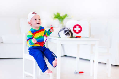 Cute laughing baby boy playing animal doctor with his pet rabbit using toy stethoscope in a white nursery room