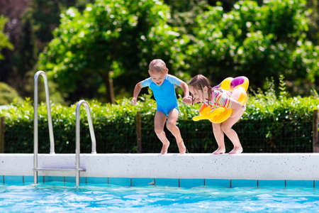 pool diving: Happy little girl and boy holding hands jumping into outdoor swimming pool in a tropical resort during family summer vacation. Kids learning to swim. Water fun for children.
