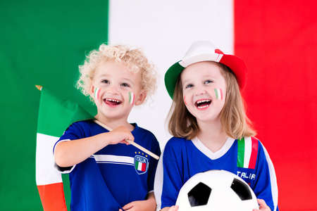 Children cheering and supporting Italian national football team. Kids fans and supporters of Italy during soccer championship.