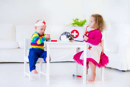 stethoscope boy: Two happy children, cute toddler girl and adorable baby boy, brother and sister, playing doctor and veterinary hospital with real rabbit using stethoscope toy and medical uniform, having fun at home or preschool with animals Stock Photo