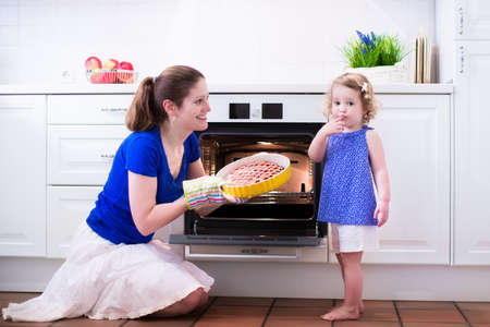 kitchen device: Mother and child bake a pie. Young woman and her daughter cook in a white kitchen. Kids baking pastry. Children helping to make dinner. Modern interior with oven and other appliances. Family eating.