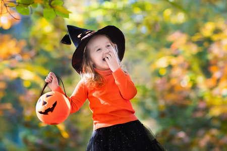 가 공원에서 노는 마녀 의상에서 어린 소녀입니다. 할로윈 트릭이나 치료에서 아이 재미. 아이 트릭이나 치료. 잭 - 오 - 랜턴 유아 아이. 가을 숲에서