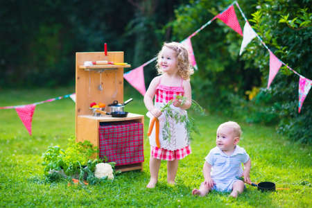 Kids playing with a toy kitchen. Children play in a summer garden. Boy and girl cooking and baking healthy vegetables in the backyard. Toddler child and baby cook together. Outdoor fun in summer.
