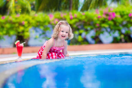 sea flowers: Beautiful little girl, cute toddler with curly hair wearing a red summer dress, sitting at a swimming pool drinking water melon juice with fresh fruit having fun during family vacation in a tropical resort