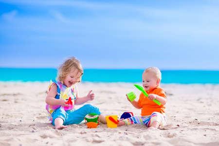 Kinderen spelen op een strand. Kinderen bouwen zandkastelen op het tropische eiland. Zomer waterpret voor familie. Jongen en meisje met speelgoed emmers en schop op de kust. Ocean vakantie met baby en peuter kind.