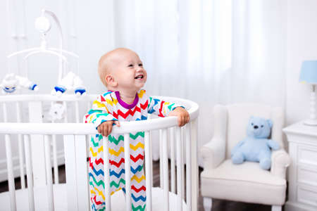 Cute laughing baby standing in bed after nap time. Nursery interior for young kids. Adorable little boy playing in his crib. White furniture for children bedroom.