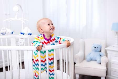 Leuke lachende baby die zich in bed na dutje tijd. Kwekerij interieur voor jonge kinderen. Schattige kleine jongen spelen in zijn wieg. Witte meubels voor kinderen slaapkamer.