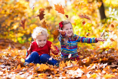 children at play: Happy children playing in beautiful autumn park on warm sunny fall day. Kids play with golden maple leaves. Stock Photo