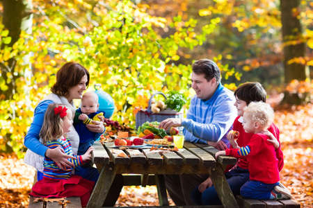 family outside: Happy young family with four children grilling meat and making sandwich and salad on a picnic table in sunny autumn park. Barbeque fun for parents with kids on warm fall day. Grill and BBQ party.