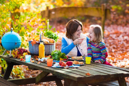 picnic food: Happy young mother with little girl grilling meat and making sandwich and salad on a picnic table in sunny autumn park. Barbeque fun for parents with kids on warm fall day. Grill and BBQ party. Stock Photo