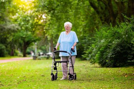 은퇴 개념 동안 그녀의 워커 나 휠체어, 원조와 지원을 밀어 화창한 공원에서 산책을 즐기는 도보 장애를 가진 행복 수석 장애인 아가씨. 스톡 콘텐츠