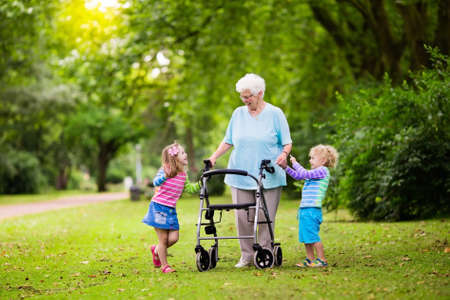 boy lady: Happy senior lady with a walker holding hands of little boy and girl. Grandmother with grand children enjoy a walk in summer park. Kids supporting disabled grandparent.